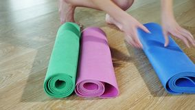 La mujer joven que pone una estera de la yoga, presenta una estera de la aptitud metrajes