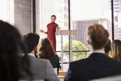 La mujer joven que presenta seminario del negocio gesticula a la audiencia Fotos de archivo
