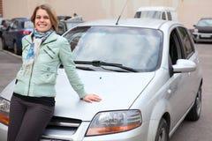 La mujer joven que se coloca detrás de un nuevo posee el coche Imagen de archivo