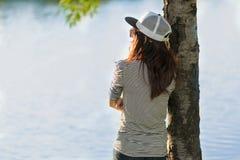 La mujer joven que se coloca en la orilla del río debajo de árbol y ella miran gusto Foto de archivo