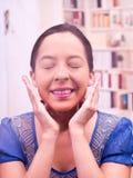 La mujer joven que se lava la cara con ambas manos, observa cerrado y la sonrisa Imágenes de archivo libres de regalías