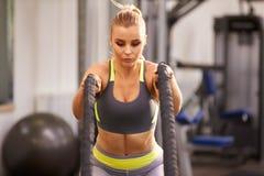 La mujer joven que se prepara para resolverse con batalla ropes en un gimnasio Imagenes de archivo