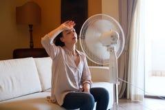 La mujer joven que se relaja debajo del aire aviva en casa imagen de archivo libre de regalías