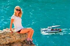 La mujer joven que se relaja en el acantilado rocoso con el mar azul y la nave navegan en fondo Fotografía de archivo