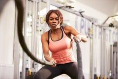 La mujer joven que se resuelve con batalla ropes en un gimnasio Foto de archivo