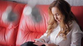 La mujer joven que se sentaba en un sofá de cuero rojo y las hojas fijó de fotos metrajes