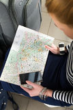 La mujer joven que se sienta con una tableta y está mirando el mapa Primer recolectado en un viaje Foto de archivo