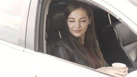 La mujer joven que se sienta en coche y que sostiene el caf? en sus manos, cierra la ventanilla del coche almacen de metraje de vídeo