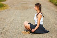 La mujer joven que se sienta en el camino y que medita, se relaja imagen de archivo