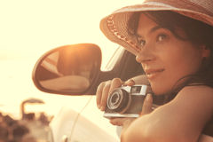 La mujer joven que se sienta en el coche, alista para tomar una foto Imagen de archivo