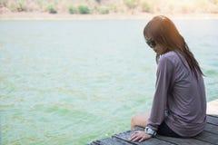 La mujer joven que se sienta en el frente de madera de la balsa de sí misma es wat azul Fotografía de archivo libre de regalías