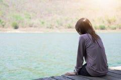 La mujer joven que se sienta en el frente de madera de la balsa de sí misma es wat azul Imágenes de archivo libres de regalías