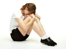 La mujer joven que se sienta en el suelo en deporte arropa Foto de archivo libre de regalías