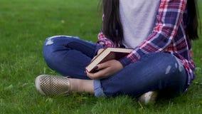 La mujer joven que se sienta en la hierba, sosteniendo el libro cerrado, actividad recreativa, se relaja almacen de video