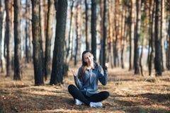 La mujer joven que se sienta en la hierba en el bosque el día soleado, demostraciones manosea con los dedos para arriba fotos de archivo