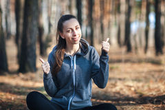 La mujer joven que se sienta en la hierba en el bosque el día soleado, demostraciones manosea con los dedos para arriba foto de archivo libre de regalías
