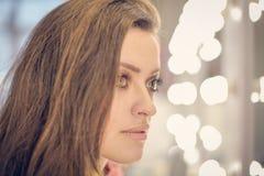 La mujer joven que se sienta en salón de belleza está presentando en la cámara Imagen de archivo libre de regalías