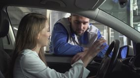 La mujer joven que se sienta en un coche hermoso, y el automaster en la ventana habla de la parte técnica de usar el coche almacen de metraje de vídeo