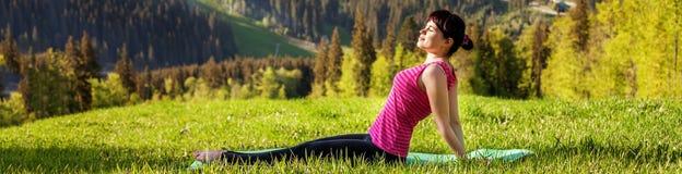 La mujer joven que se sienta en una cima de la montaña Bandera para el sitio web T imágenes de archivo libres de regalías