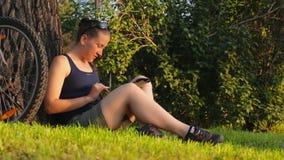 La mujer joven que se sienta en una hierba verde debajo de árbol en las aplicaciones del parque hace tabletas la PC, bici almacen de video
