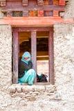 La mujer joven que se sienta en ventanas de un monasterio atraviesa la observación de un relig imagenes de archivo