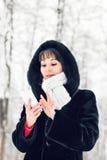 La mujer joven que sonríe con el teléfono elegante y el invierno ajardinan Imagenes de archivo