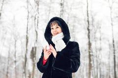 La mujer joven que sonríe con el teléfono elegante y el invierno ajardinan Fotografía de archivo libre de regalías