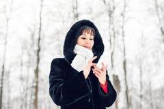 La mujer joven que sonríe con el teléfono elegante y el invierno ajardinan Foto de archivo