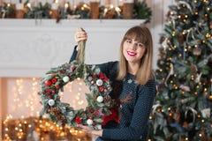 La mujer joven que sostiene una guirnalda de la Navidad con el abeto ramifica para el día de fiesta La celebración del Año Nuevo  Imagen de archivo libre de regalías
