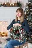 La mujer joven que sostiene una guirnalda de la Navidad con el abeto ramifica para el día de fiesta La celebración del Año Nuevo  Imágenes de archivo libres de regalías
