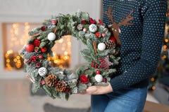 La mujer joven que sostiene una guirnalda de la Navidad con el abeto ramifica para el día de fiesta La celebración del Año Nuevo  Foto de archivo libre de regalías