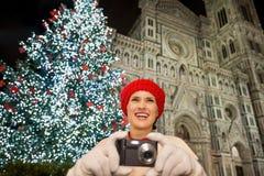 La mujer joven que toma las fotos acerca al árbol de navidad en Florencia, Italia Foto de archivo libre de regalías