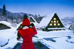 La mujer joven que toma una foto en Shirakawa-va pueblo en invierno, sitios del patrimonio mundial de la UNESCO, Japón imágenes de archivo libres de regalías