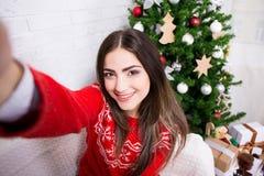 La mujer joven que tomaba la foto del selfie cerca adornó el árbol de navidad imagenes de archivo