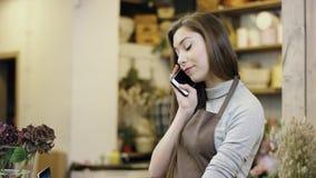 La mujer joven, que trabaja en floristería, hablando por el teléfono y mecanografiando algo en su ordenador portátil, cámara va d metrajes
