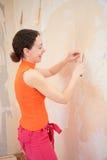 La mujer joven quita los papeles pintados viejos Imágenes de archivo libres de regalías