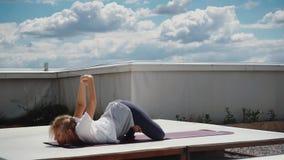 La mujer joven realiza asanas avanzados de la yoga de Hatha está mintiendo en la estera de la yoga metrajes