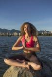 La mujer joven reflexiona sobre una roca en el océano, sonriendo Imágenes de archivo libres de regalías