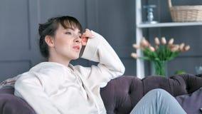 La mujer joven relajada cansada que estira el aumento da sentarse en el sofá en interior acogedor del suéter en casa almacen de metraje de vídeo