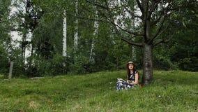 La mujer joven relajada está leyendo un libro debajo de la sombra del árbol durante vacaciones de verano en el campo almacen de metraje de vídeo
