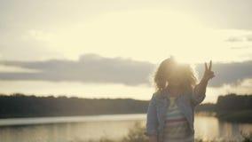 La mujer joven rizada linda en una chaqueta de los vaqueros corre abajo de la orilla del lago a la puesta del sol brillante, desp almacen de metraje de vídeo