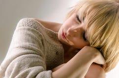 La mujer joven rubia de Sleaping se vistió en suéter y el asiento blancos grandes de la cachemira en el entero-piso blanco Imagen de archivo