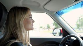 La mujer joven rubia está conduciendo un coche en la ciudad que lleva a cabo las manos en el volante metrajes