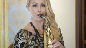 La mujer joven rubia hermosa está tocando el saxofón La muchacha atractiva en vestido negro de oro juega el saxofón en casa o el  metrajes