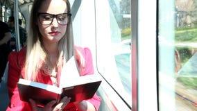 La mujer joven rubia hermosa lee el libro mientras que monta la tranvía metrajes
