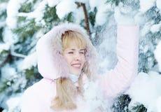 La mujer joven rubia hermosa sacude nieve abajo de la rama de árbol de pino y disfruta en invierno Imagenes de archivo