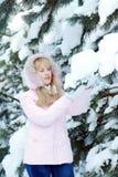 La mujer joven rubia hermosa se vistió en ramas de árbol nevosas de pino de los tactos rosados de la chaqueta fotos de archivo
