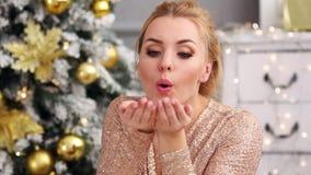 La mujer joven rubia hermosa sopla un confeti de las manos cerca del árbol de navidad almacen de video