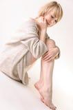 La mujer joven rubia se vistió en suéter y el asiento blancos grandes de la cachemira en el entero-piso blanco Imagenes de archivo