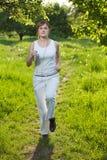 La mujer joven runing en un parque y escucha la música Imagen de archivo libre de regalías